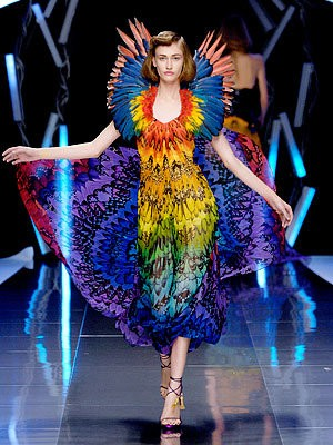 A model walks in a rainbow feathered dress in McQueen's Spring/Summer 2003 show.