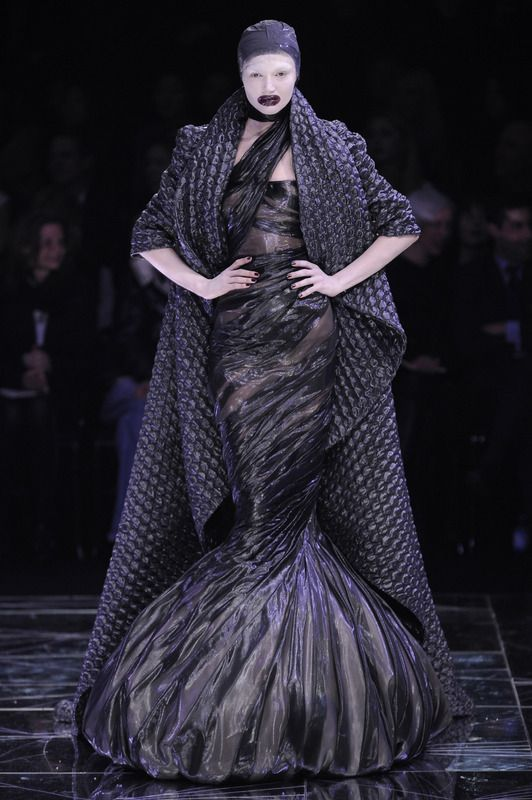"""A model walks the """"Horn of Plenty"""" runway in a dress made of garbage bags and a coat made of bubblewrap."""