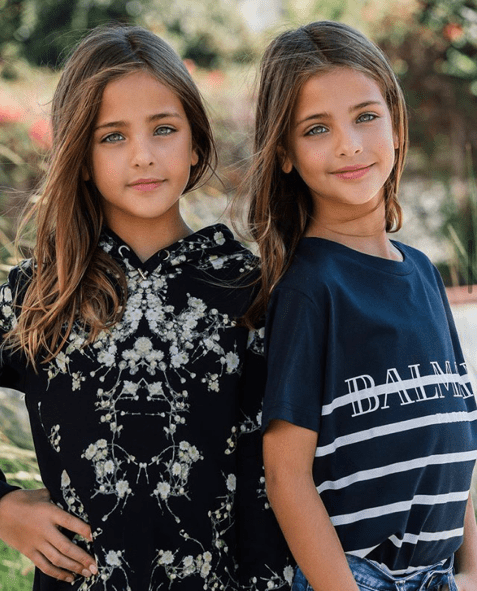 The Clements twins pose in designer outfits. Image via @theclementstwins Instagram.