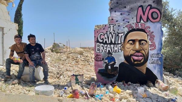 Black Lives Matter everywhere - Syrian painters Aziz Asmar and Anis Hamdoun sit next to a graffiti of George Floyd in Idlib, Syria.