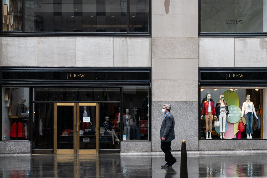 A man walks by a closed J. Crew in New York City.