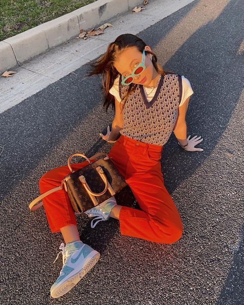 Internet favorite Emma Chamberlain tucks in her sweater vest for a more pinned look, paired with bright jeans and a head tilt made for the camera.
