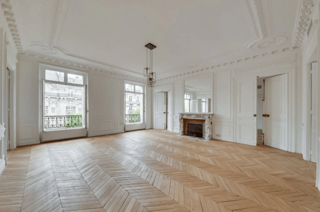 Natural light, a marble fireplace, herringbone hardwoods, and original moldings make this room the focal point of the apartment.