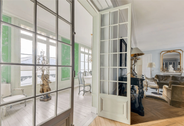 Natural light flows throughout the home, aided by original French doors and an enclosed porch.
