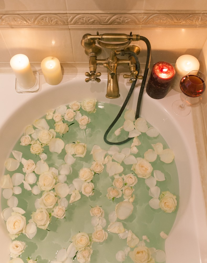 Rose petals, wine, candles, and epsom salt make the perfect bath.