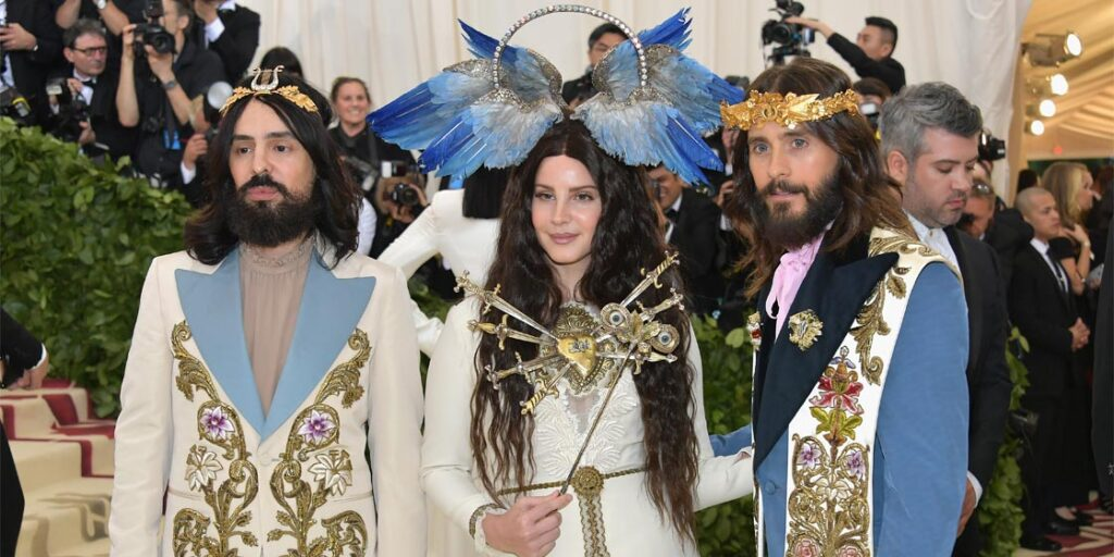 From left, Alessandro Michele walks the Met Gala red carpet with Lana del Ray and Jared Leto.